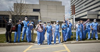SHN health care workers wave on the curb outside the hospital